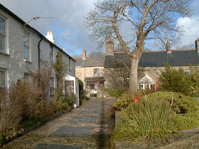 Terraced cottages to the left of a walkway with stone walled gardens to the right. In the background are other cottages.